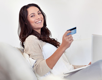 Buy stock photo Portrait of an attractive woman holding a credit card while using a laptop