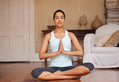 Buy stock photo Full length shot of a young woman doing yoga in her living room