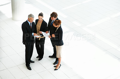 Buy stock photo High-angle view of a group of businesspeople discussing paperwork in an office lobby