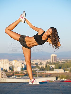 Buy stock photo Shot of a beautiful young woman exercising on top of a building against the backdrop of a city
