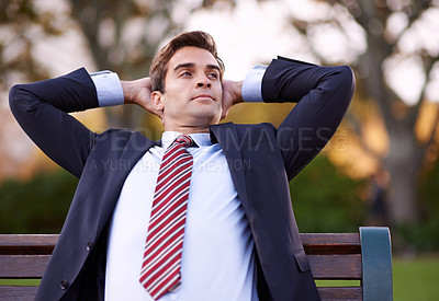 Buy stock photo A content businessman sitting with his hands behind his head on a park bench