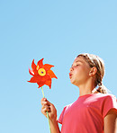 Cute girl playing with a pinwheel against the blue sky