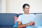 Happy man surfing his laptop at home