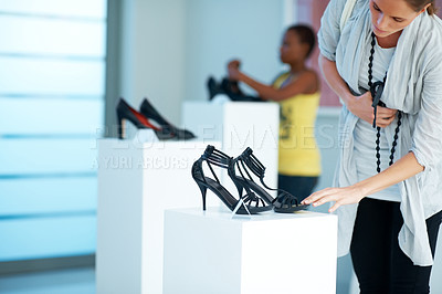 Buy stock photo Cute young woman selecting shoes at a store