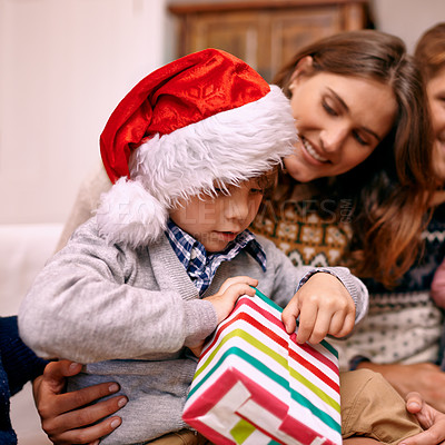 Buy stock photo Shot of a little boy opening up a gift at Christmas