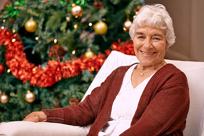Buy stock photo A happy senior woman sitting on a couch with a Christmas tree behind her