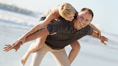 Buy stock photo A husband giving his wife a piggyback ride on the beach
