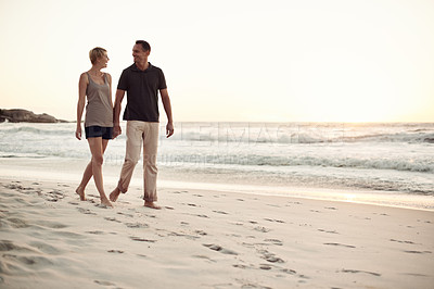 Buy stock photo Shot of a mature couple taking a stroll on the beach