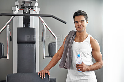 Buy stock photo A young ethnic man standing next to an exercise machine at the gym