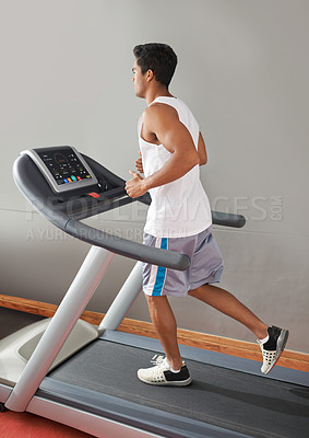 Buy stock photo A young ethnic man running on a treadmill