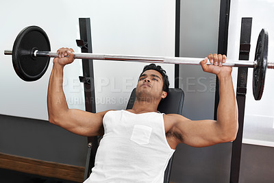 Buy stock photo A young ethnic man lifting a heavy barbell in the gym