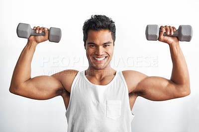 Buy stock photo Studio portrait of an athletic young man holding up dumbbells