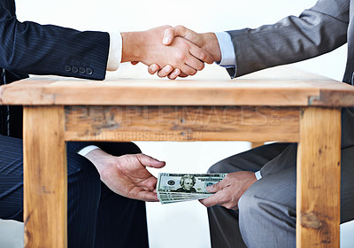Buy stock photo Cropped shot of two businessmen shaking hands while money passes hands under a table