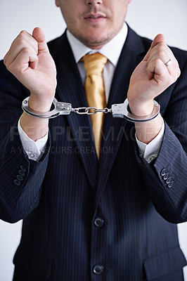 Buy stock photo Cropped shot of a businessman wearing handcuffs