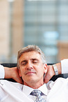 Closeup of a senior business man relaxed with hands behind his head