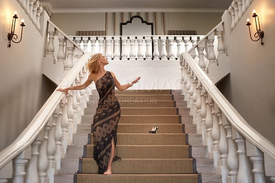 Buy stock photo A young woman losing a shoe while running down a magnificent staircase
