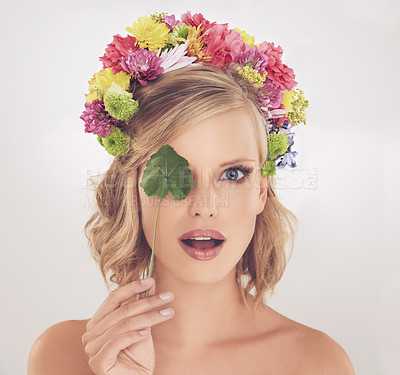 Buy stock photo A young woman with flowers in her hair covering her one eyes with a leaf