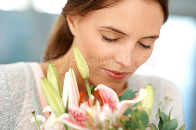 Buy stock photo Gorgeous young woman enjoying smelling flowers