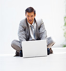 Happy young business man sitting on the floor and working on a laptop