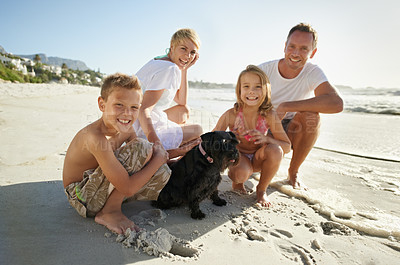 Buy stock photo A family having fun at the beach with their pet dog