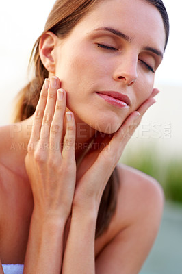 Buy stock photo Beautiful young lady pampering her face