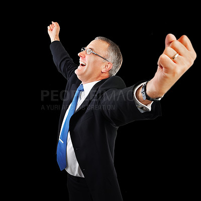 Buy stock photo Studio shot of a mature businessman celebrating a success against a black background