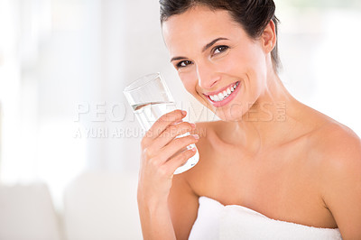 Buy stock photo Portrait of a beautiful woman smiling while holding a glass of water