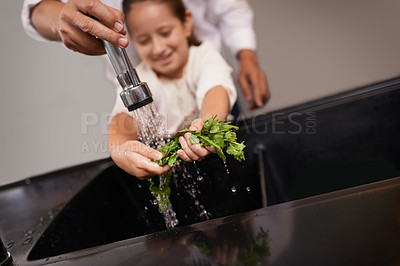 Buy stock photo Shot of a little girl washing vegetables at the sink with the help of her grandfather