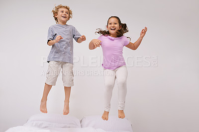 Buy stock photo Shot of two little children jumping on a bed