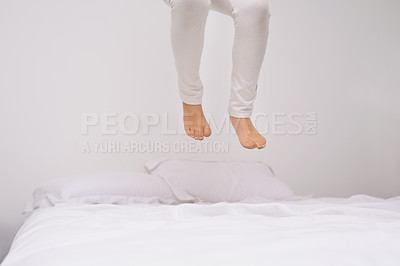 Buy stock photo Cropped shot of the legs of a little girl jumping on the bed