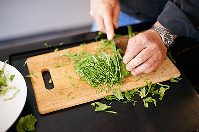 Buy stock photo Cropped shot of a senior man chopping up herbs in his kitchen
