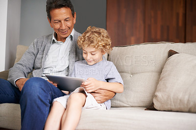 Buy stock photo A grandfather sitting with his grandson while he's using a digital tablet