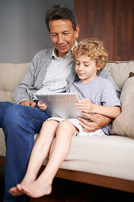 Buy stock photo A young boy showing his grandfather his new digital tablet