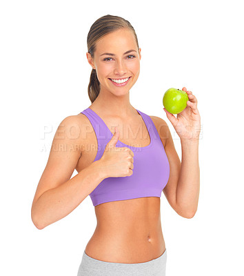 Buy stock photo Studio portrait of a sporty young woman holding an apple and giving you the thumbs up
