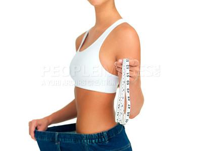 Buy stock photo Cropped shot of a sporty woman holding out a tape measure while pulling her pants away from her body