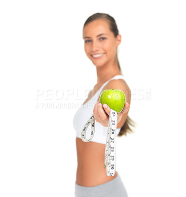 Buy stock photo Portrait of a sporty young woman holding out an apple and a tape measure isolated on white