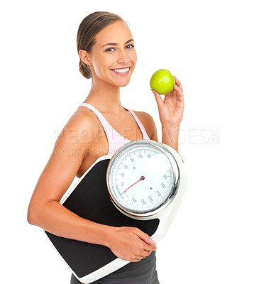 Buy stock photo Studio portrait of an attractive young woman holding an apple and a weight scale