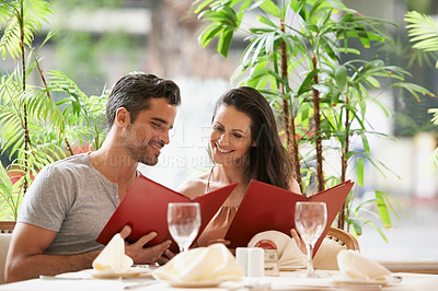 Buy stock photo A happy young couple looking at their menu's at a fancy restaurant