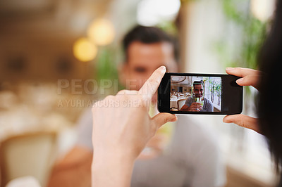 Buy stock photo A woman taking a picture of her partner while dining out at a fancy restaurant
