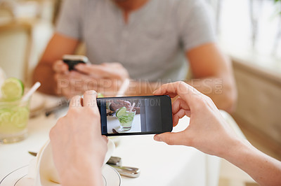 Buy stock photo A woman taking a picture while dining out with her partner at a restaurant