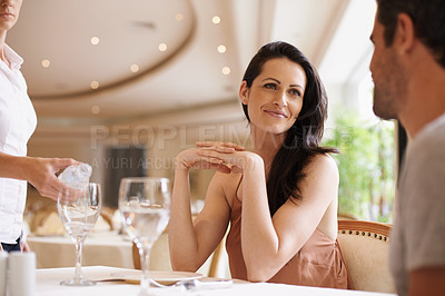 Buy stock photo A young couple sitting at a table in a restaurant