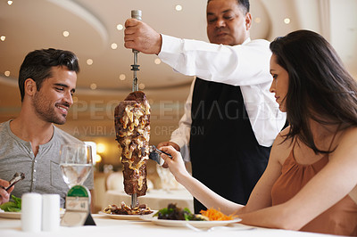 Buy stock photo A happy couple being served a meat dish at a fine dining restaurant