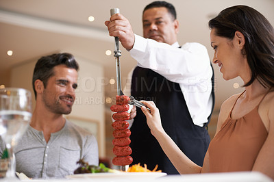 Buy stock photo A happy couple having a meat dish at a fine dining restaurant