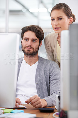 Buy stock photo Shot of a young businesswoman looking over her colleague's shoulder at his computer