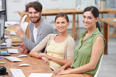 Buy stock photo Shot of a smiling group of young businesspeople at their desk