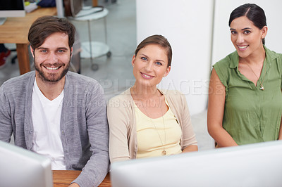 Buy stock photo Shot of a group of young businesspeople sitting together at a workstation
