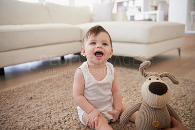 Buy stock photo Cropped shot of a baby boy sitting on the carpet at home with a plush toy