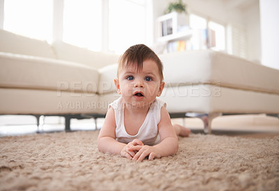 Buy stock photo Cropped shot of a baby lying on his stomach on the carpet