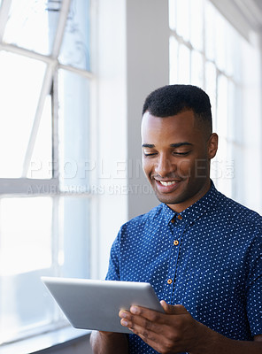 Buy stock photo A young ethnic man working on a tablet while standing next to a window