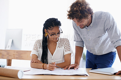 Buy stock photo An attractive young man and his female business partner discussing designs